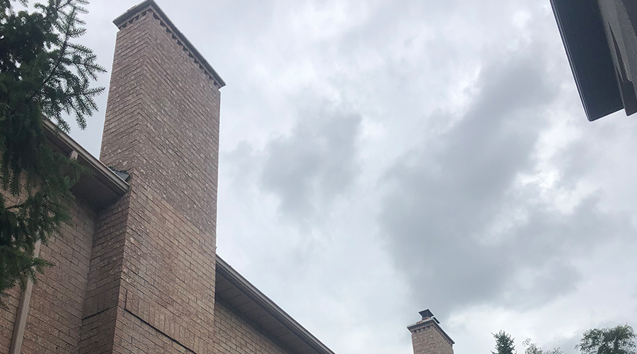 Brick chimneys on an old apartment building in Toronto repaired by Mace Masonry