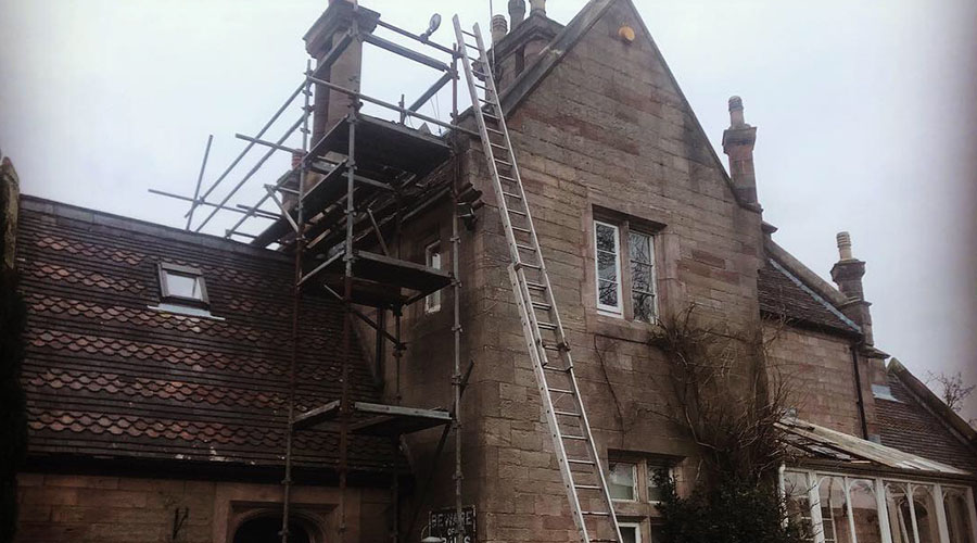 Old stone house with scaffolding during a heritage restoration project by Mace Masonry