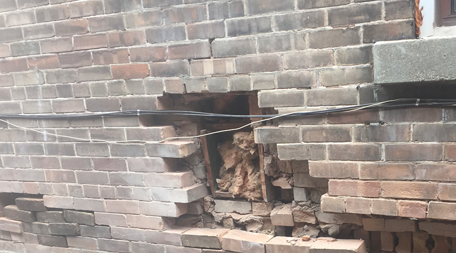 Old brick building with many missing bricks before a repair project by Mace Masonry