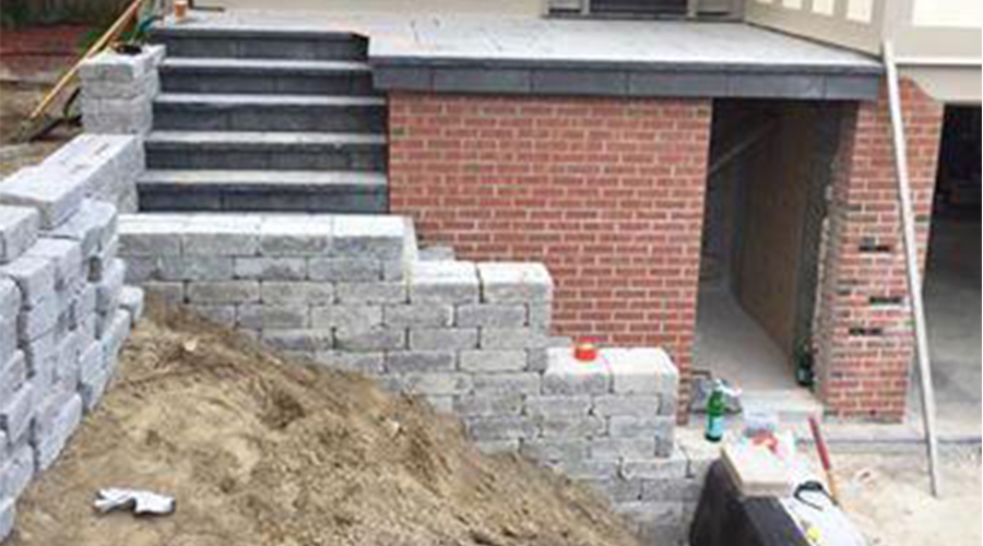 Stone retaining wall and steps under construction by Mace Masonry
